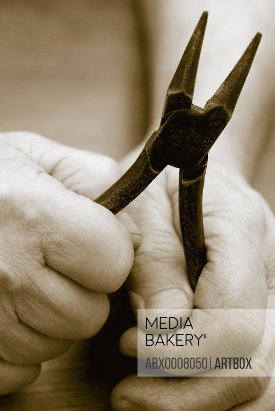 Close-up of a person's hands holding a pair of pliers