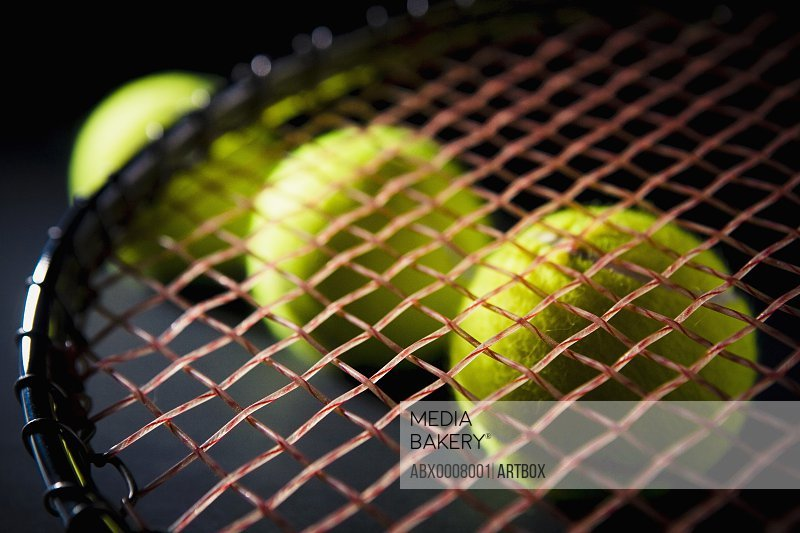 Close-up of three tennis balls with a tennis racket