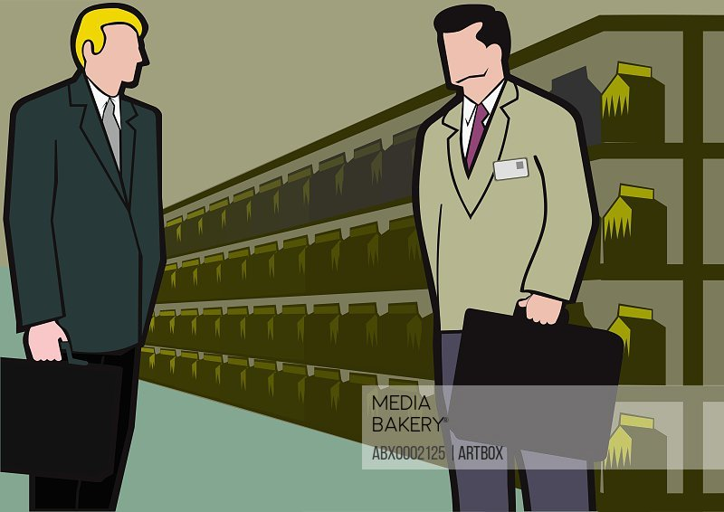 Two businessmen standing in front of shelves