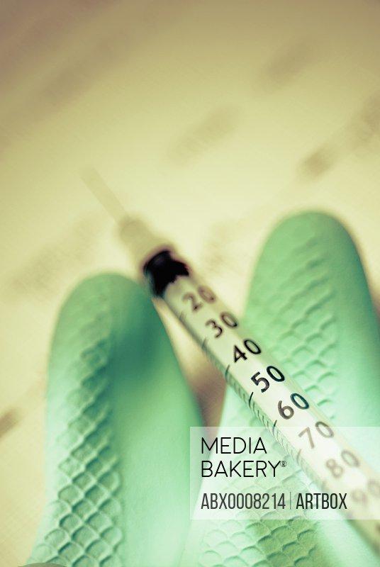 Syringe on a glove