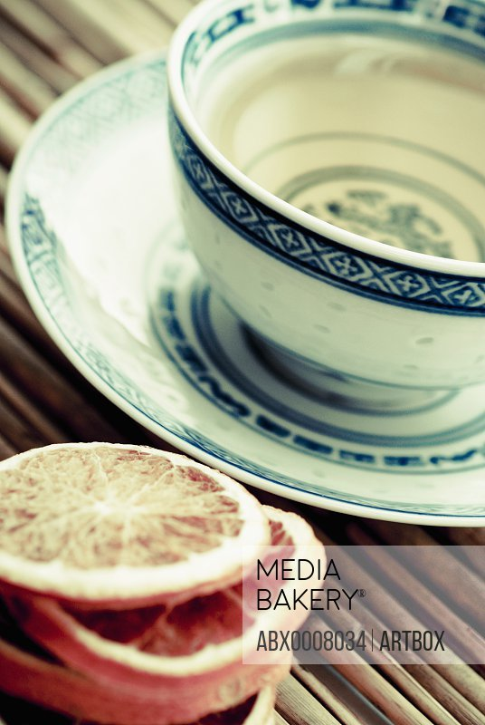 Close-up of a tea cup with lemon slices