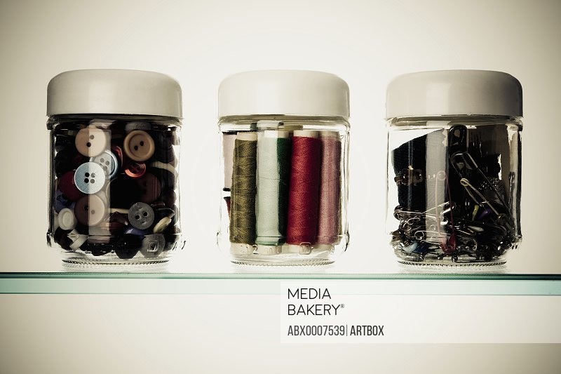 Close-up of buttons and safety pins with thread spools in three different jars