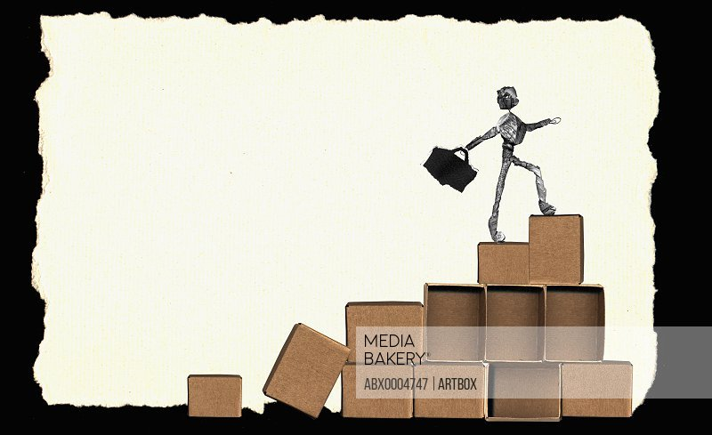 Close-up of a newspaper figurine walking on boxes