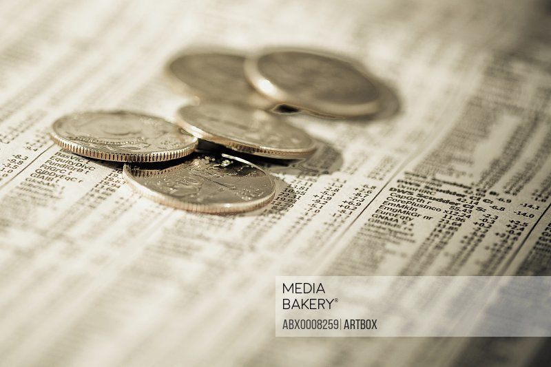 Close-up of coins on a financial newspaper