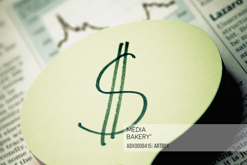 Close-up of a dollar sign on a financial newspaper