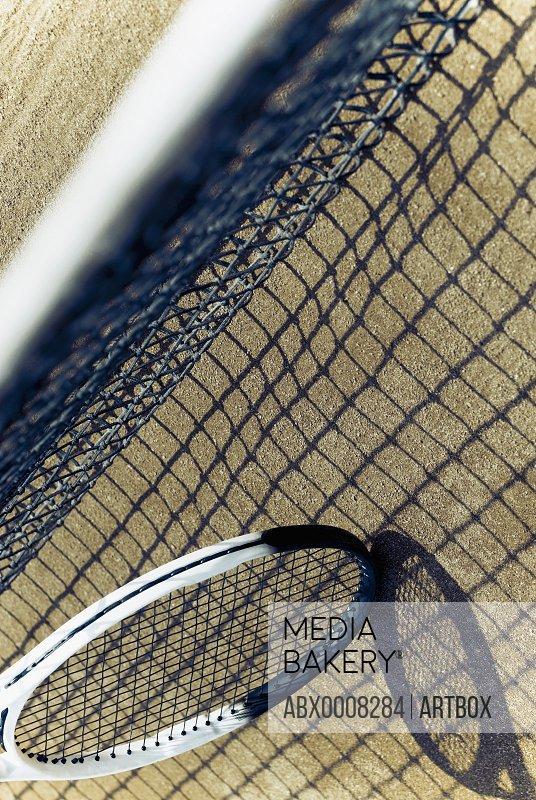 Close-up of a tennis net with a tennis racket