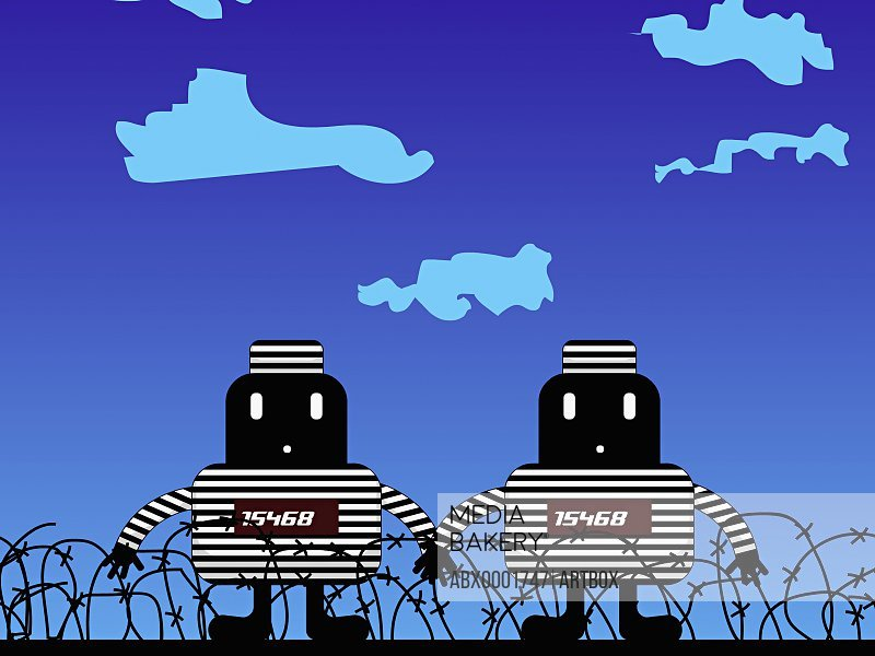 Two robots standing between a barbed wire fence