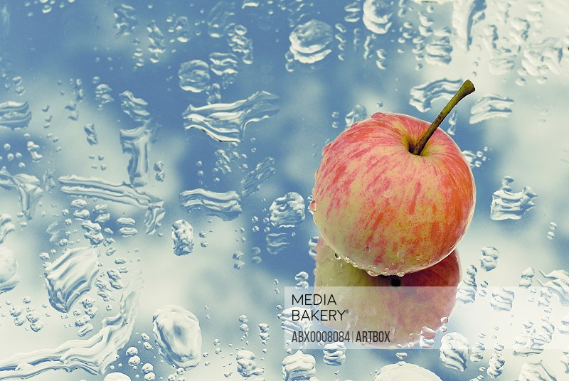 Close-up of an apple on a wet glass