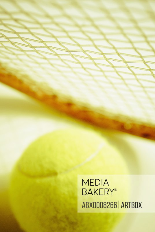 Close-up of a tennis ball with a tennis racket