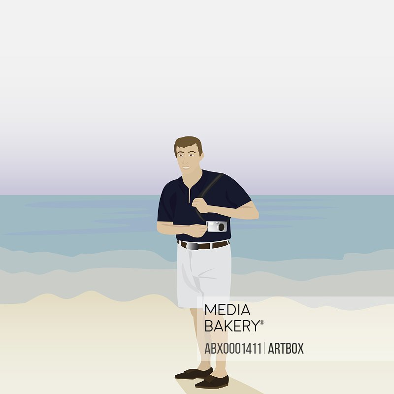 Man standing on the beach and holding a camera