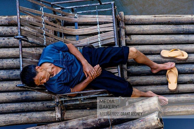 Chinese Man Sleeping On A Raft, Li River, Yangshuo, Guangxi Province, China.