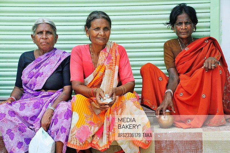 Pilgrim women having rest by the street