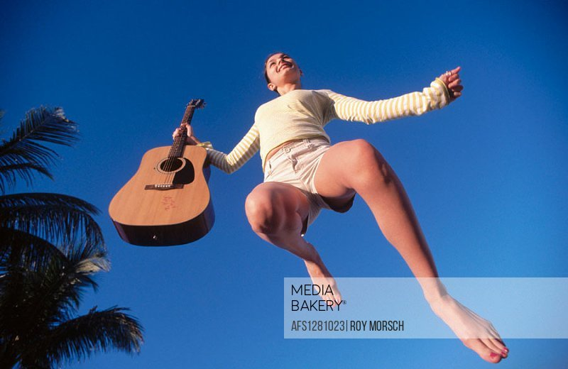 Jumping for joy with guitar in hand