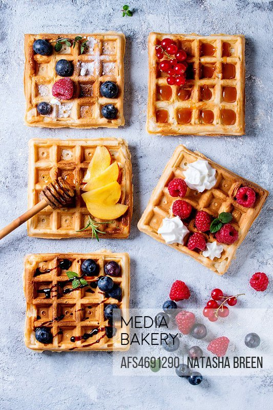 Homemade square belgian waffles with fresh ripe berries blueberry, raspberry, red currant, peach served with caramel, balsamic sauce, honey, whipped c...