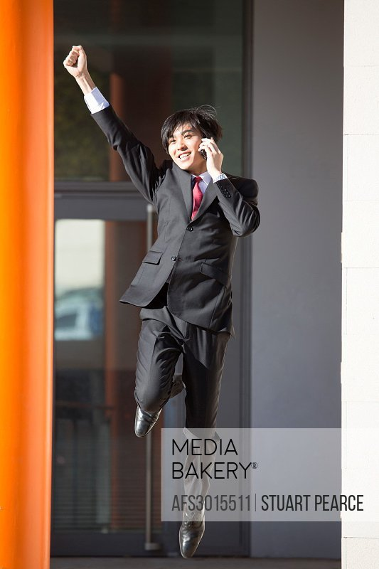 Young Asian businessman jumping for joy