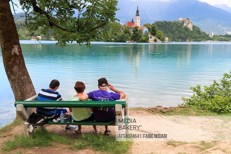 Tourists sitting on a bench on the bank of lake Bled. Church of background.