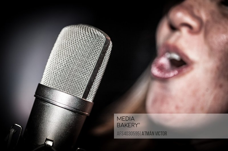 woman speaking or singing with a microphone