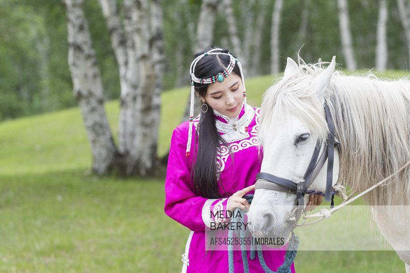 China, Inner Mongolia, Hebei Province, Zhangjiakou, Bashang Grassland, Mode, Mongol woman traditionnaly dressed with a horse, .