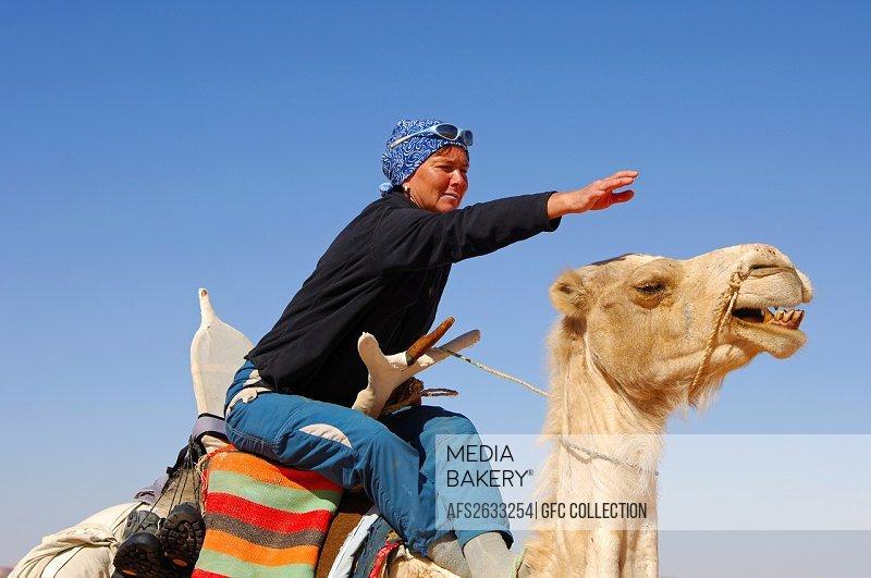 Tourist caressing his camel on a ride, Sahara desert, Libya