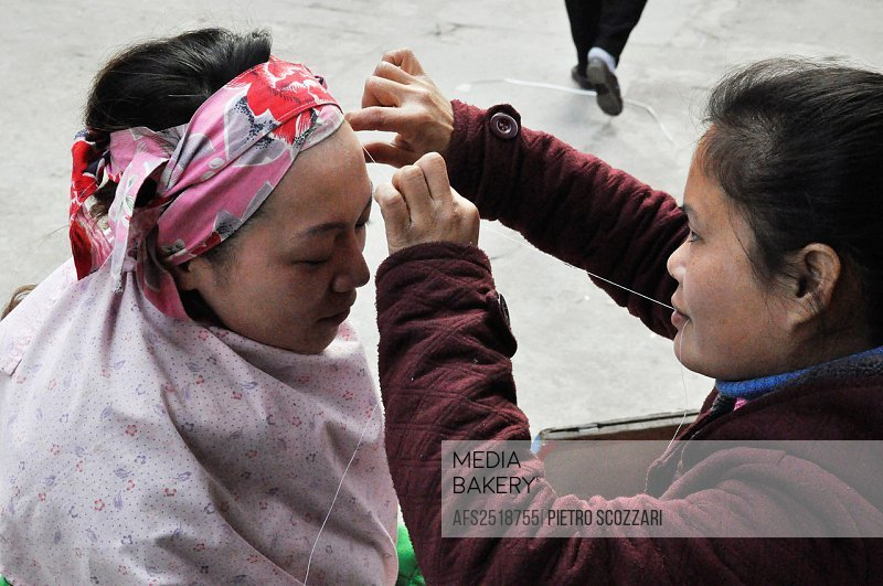Dongguan (China): a street beautician plucking a client's eyebrows with a thread in the Changping District