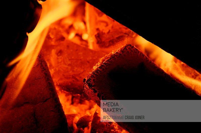 Orange glowing embers in a small wood bonfire