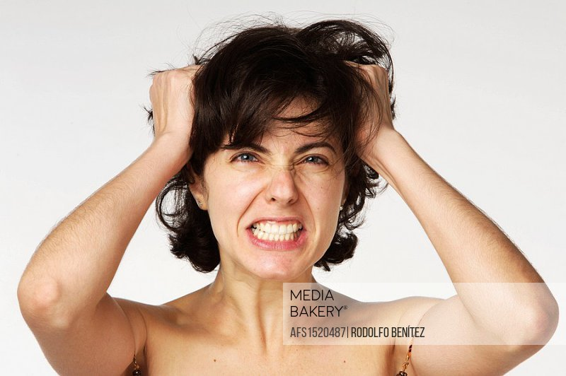 Young woman in her 30s desperately grabbing her hair
