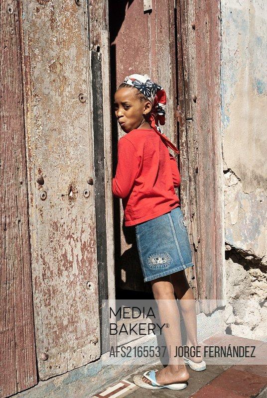 Girl entering home and looking curious to the camera, Santiago de Cuba, Cuba, Caribbean
