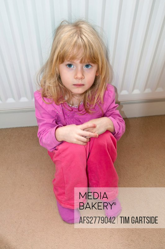 young girl sitting on floor looking worried