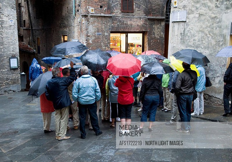 Italy, Tuscany, Siena. Group of tourists on tour of the old city on a rainy day, crowd together to hear tour guide.