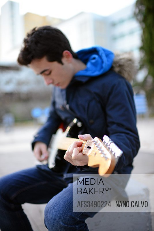 Exterior portrait of teenager playing the electric guitar.