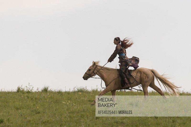 China, Inner Mongolia, Hebei Province, Zhangjiakou, Bashang Grassland, Woman Mongol on a horse