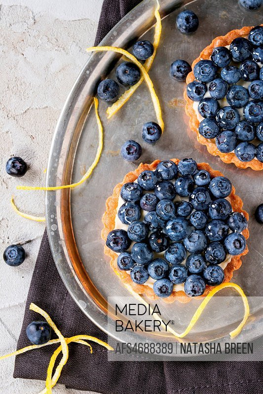 Two Lemon tartlets with fresh blueberries, served on vintage metal tray with lemon zest and black textile napkin over gray plastered surface. Flat lay