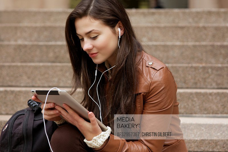 Female student studying lecture from her ipad using iTunes U application