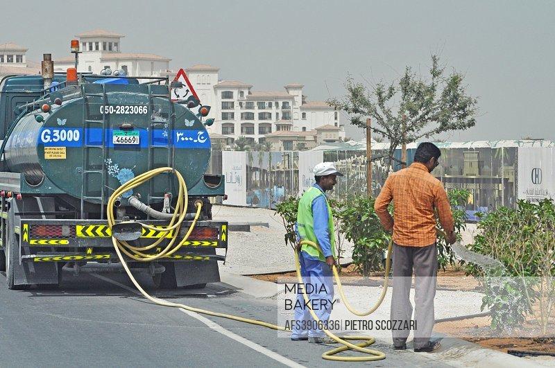 Abu Dhabi: gardeners watering plants along a road
