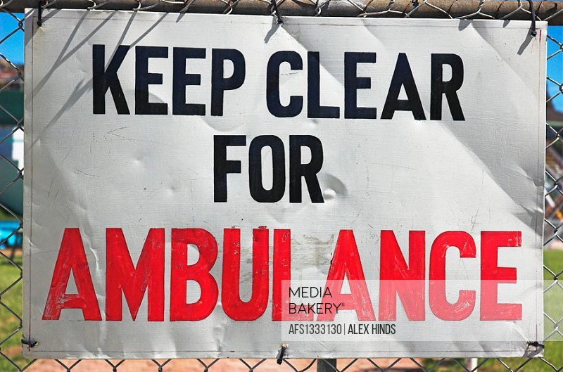 Sign on fence requesting clear access for ambulance / emergency use.
