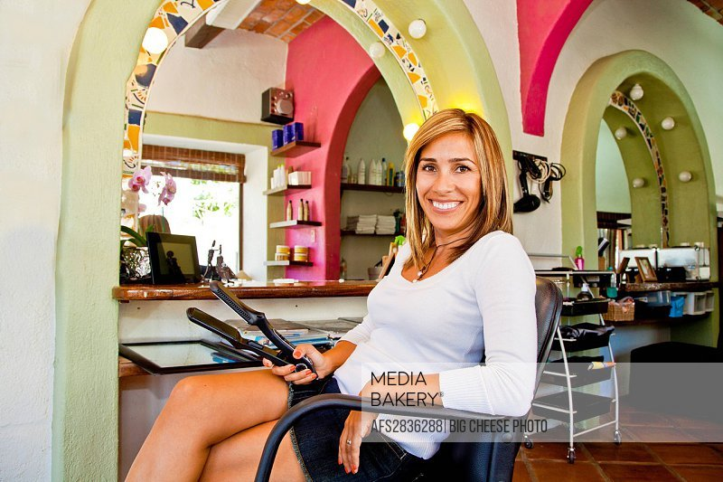 Beautician seated on chair in beauty salon