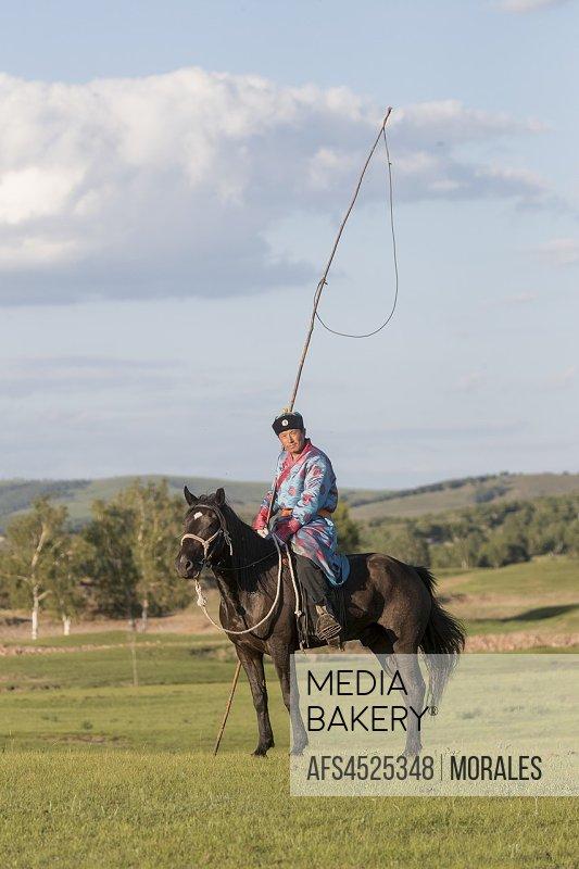 China, Inner Mongolia, Hebei Province, Zhangjiakou, Bashang Grassland, Mongolian man traditionnaly dressed with his horse.
