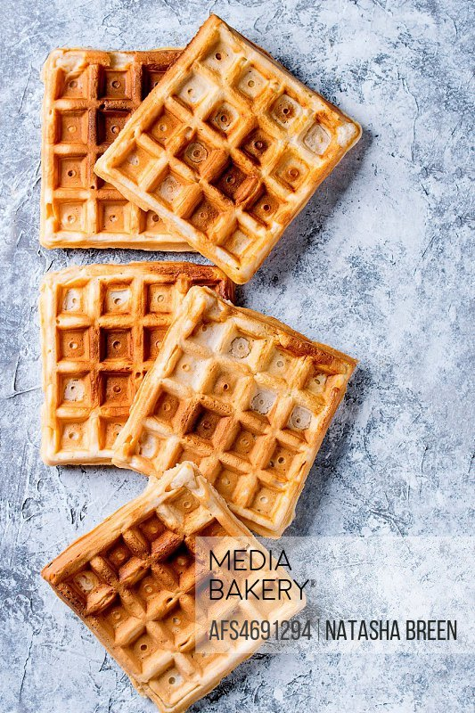 Empty homemade square belgian waffles over gray texture background. Top view with space