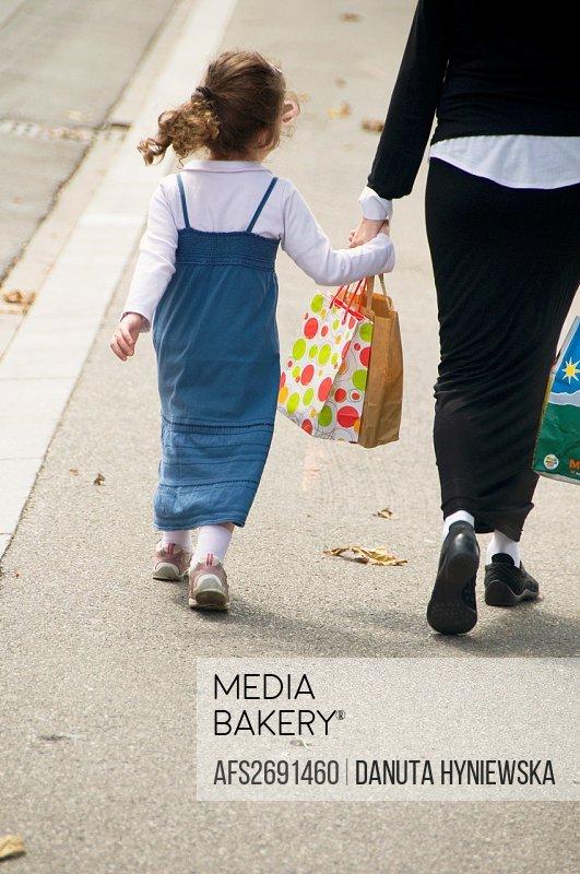 woman walking hand in hand with little girl, street scene, Geneva, Switzerland