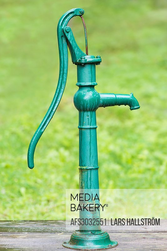 Old fashioned hand operated green water pump