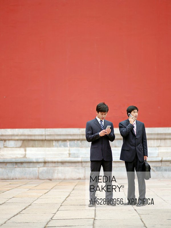 Two Chinese businessmen in suits, holding documents, having a discussion while on the phone in the Forbidden City