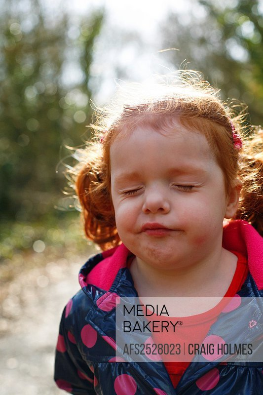 A 4 year old girl with ginger hair in pigtails looking confused