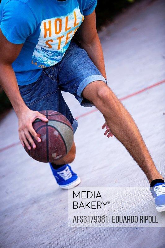 young adult playing basketball.