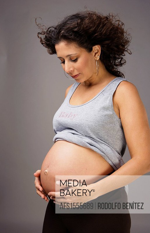 Latin pregnant woman posing in the studio looking at her belly