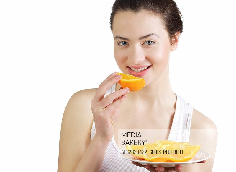 Beautiful young woman eating freshly cut oranges
