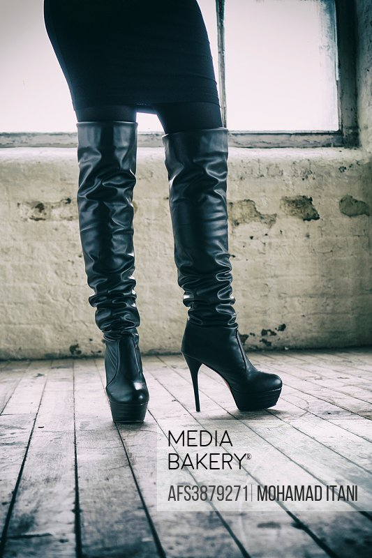 Woman wearing high leather boots indoors.