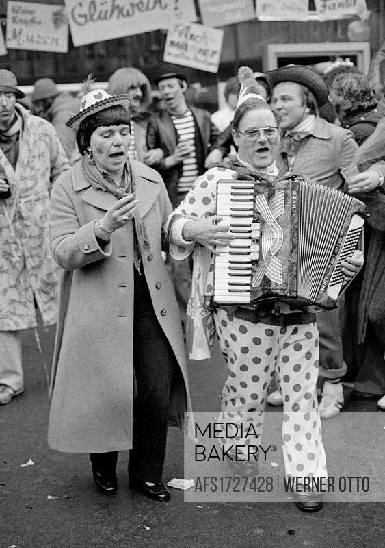 Eighties, black and white photo, people, Rhenish carnival, Rose Monday parade 1981, musician dressed in a clown suit walks along the street and plays ...