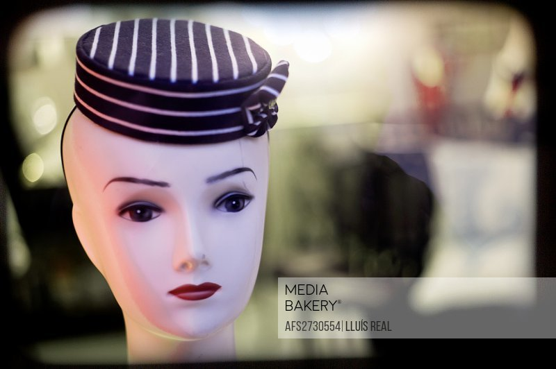 Bust of a female face with fifties style hat.