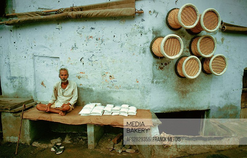 Man selling sweets in a street while seats are hanging on a wall. Ajmer, India.