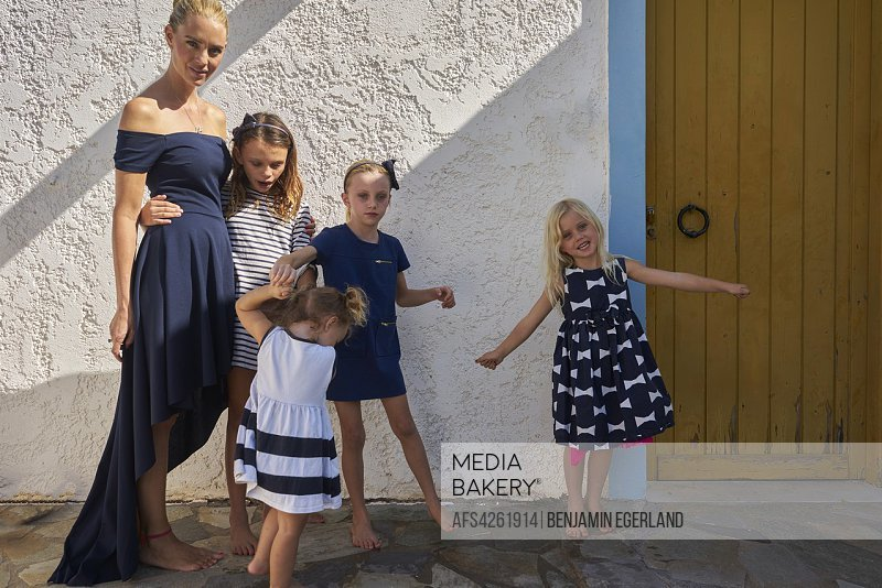 candid mother with vibrant children against house wall. Australian ethnicity